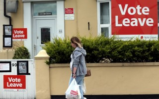 """A woman walks past a house where """"Vote Leave"""" boards are displayed in Redcar, north east England on June 27, 2016 Britain's historic decision to leave the 28-nation bloc has sent shockwaves through the political and economic fabric of the nation. It has also fuelled fears of a break-up of the United Kingdom with Scotland eyeing a new independence poll, and created turmoil in the opposition Labour party where leader Jeremy Corbyn is battling an all-out revolt.  / AFP PHOTO / Scott Heppell"""