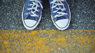 Blue Sneaker shoes standing behind the yellow line