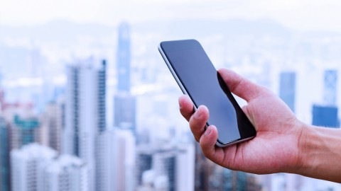 hand holding mobile phone with cityscape as background