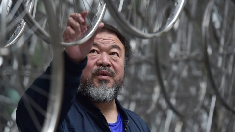 """Chinese artist Ai Weiwei touches his sculpture """"Forever"""" at the base of the the """"Gherkin"""" tower in the City of London on September 16, 2015, during a photocall to celebrate the completion of his installation, as part of the Sculpture in the City outdoor art exhibition. The nearly 10 metres tall and 16 metres wide structure consisting of 1,254 bicycle frames will be on display through May 2016.  AFP PHOTO / LEON NEAL  = RESTRICTED TO EDITORIAL USE, MANDATORY MENTION OF THE ARTIST UPON PUBLICATION, TO ILLUSTRATE THE EVENT AS SPECIFIED IN THE CAPTION ="""